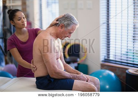 Young female therapist giving back massage to senior male patient sitting on bed at hospital ward