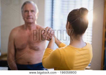 Rear view of female therapist giving arm massaging to senior male patient at hospital ward