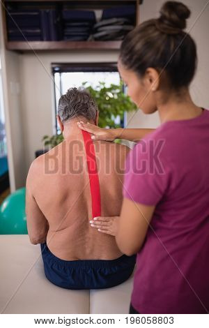 Female therapist applying elastic therapeutic tape on back of shirtless senior male patient at hospital ward