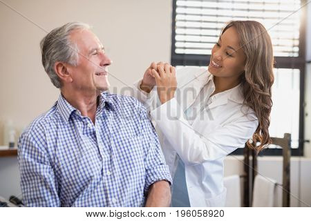 Cheerful female therapist and senior male patient looking at each other at hospital ward