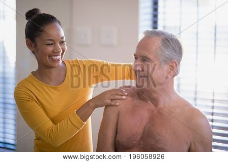 Smiling female therapist giving neck massage to shirtless senior male patient at hospital ward