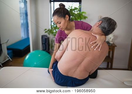 Young female therapist examining buttocks of shirtless senior male patient sitting on bed at hospital ward