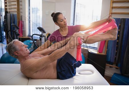 Female therapist looking at male patient pulling resistance band while lying on bed in hospital ward