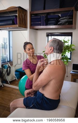 Female therapist examining neck collar of senior male patient sitting on bed at hospital ward