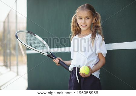 Portrait of girl holding tennis racket and ball while standing on court