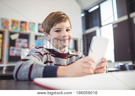 Portrait of smiling boy using mobile phone at desk in school