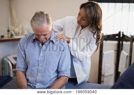 Female therapist examining neck of male patient at hospital ward