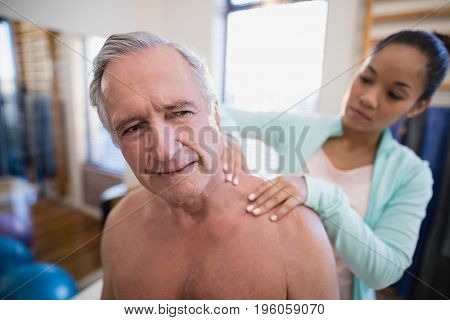 Shirtless male patient receiving neck massage from female therapist at hospital ward