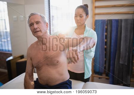 Shirtless senior male patient with arms raised receiving neck massage from female therapist at hospital ward
