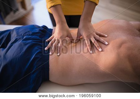Midsection of female therapist giving back massage to shirtless male patient at hospital ward