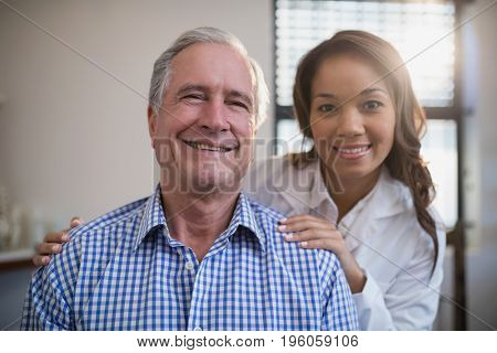 Portrait of smiling female therapist and senior male patient at hospital ward