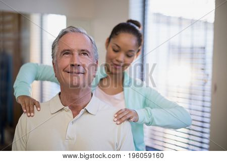 Young female therapist giving shoulder massage to senior patient at hospital ward