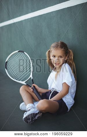 Full length portrait of girl holding tennis racket while sitting at court