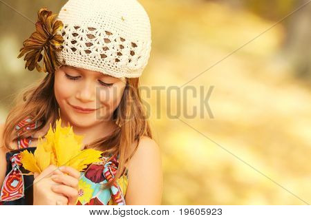 A cute young girl holding a hand-full of leaves