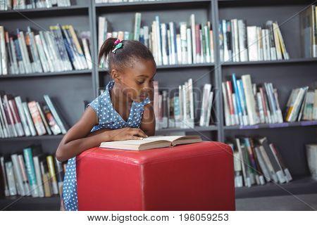 Girl reading book on ottoman against bookshelf in library