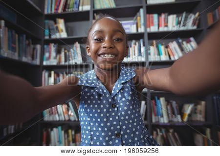 Portrait of happy girl against bookshelf in library