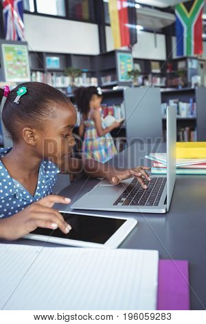 Girl using digital tablet and laptop while sitting at desk in library