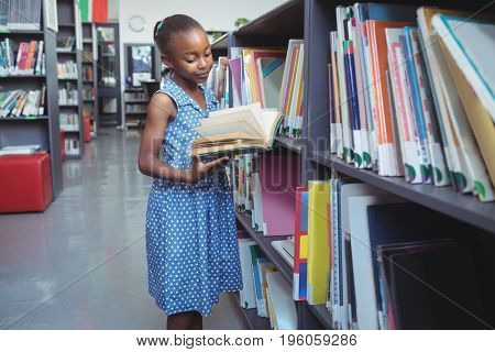 Girl reading book while standing by shelf in library