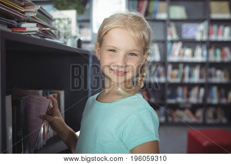 Close up portrait of girl choosing book from shelf in library