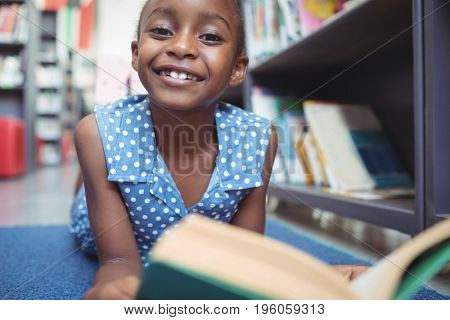 Close up portrait of smiling girl with book lying by shelf in library