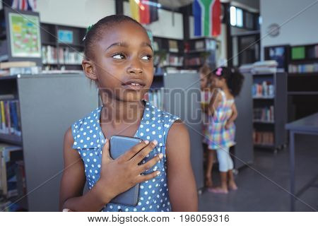 Close up of thoughtful girl holding mobile phone in library