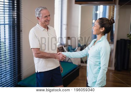 Smiling senior male patient shaking hands with female therapist at hospital ward