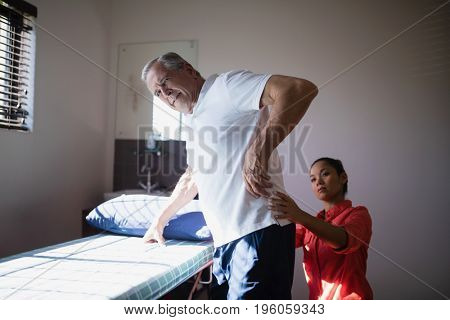 Senior man receiving back massage from female therapist at hospital ward