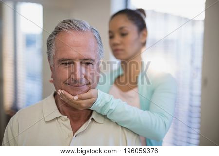 Young female therapist giving neck massage to senior patient at hospital ward
