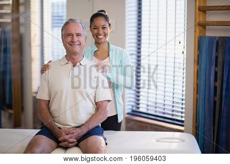 Portrait of smiling young female physiotherapist standing by male patient sitting on bed at hospital ward