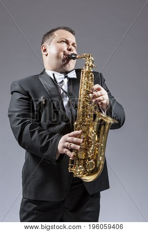 Music and Musicians Ideas and Concepts. Portrait of Caucasian Mature Expressive Saxophone Player Playing the Instrument Against White Background. Vertical Shot