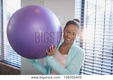 Portrait of smiling young female doctor holding purple exercise ball at hospital ward