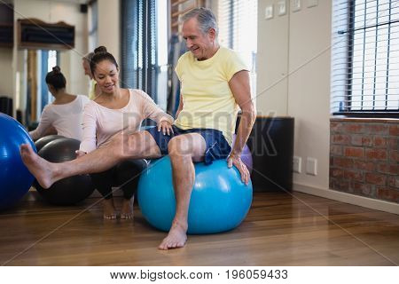 Female therapist helping senior male patient doing leg exercise on blue ball at hospital ward
