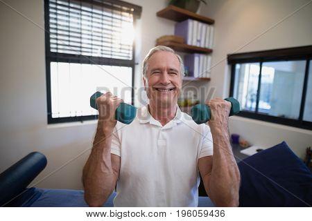 Portrait of smiling senior male patient holding dumbbells at hospital ward
