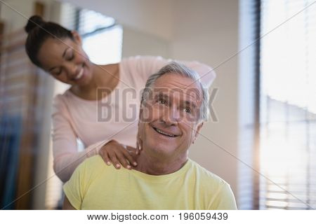 Smiling senior male patient receiving neck massage from therapist at hospital ward