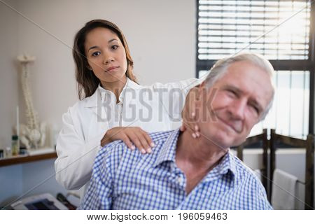 Portrait of female therapist giving neck massage to senior male patient at hospital ward