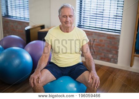 High angle view of senior male patient sitting on exercise ball with eyes closed at hospital ward