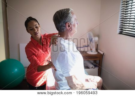 Young female therapist massaging back of senior male patient at hospital ward