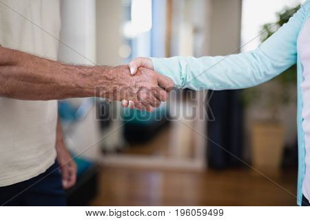 Midsection of senior male patient shaking hands with female therapist at hospital ward