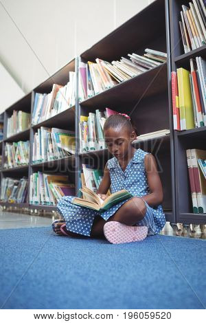 Girl reading book while sitting by bookshelf in library