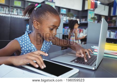 Girl using tablet computer and laptop while sitting at desk in library