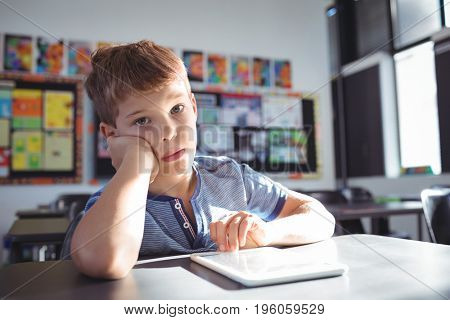 Portrait of boy leaning on desk while studying in classroom