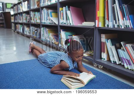Girl reading book while lying by shelf in library