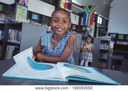 Portrait of girl with book at desk in library