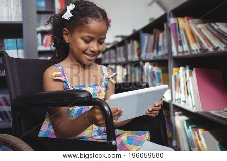 Girl on wheelchair smiling while using digital tablet in library