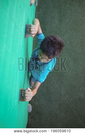 High angle view of boy gripping climbing holds on wall