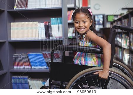 Portrait of smiling girl sitting on wheelchair at library