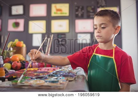Boy painting at desk in class at art studio