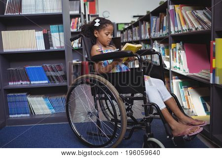 Girl reading book while sitting on wheelchair by shelves in library