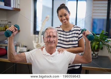 Portrait of smiling female doctor standing with male patient lifting dumbbells at hospital ward