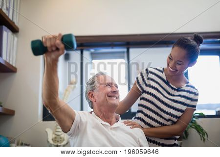 Smiling senior male patient lifting dumbbell while looking at female doctor in hospital ward